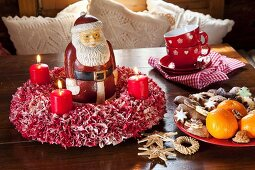 Hand-made, red and white fabric wreath with red candles and Father Christmas figurine on wooden table