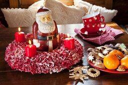 Rot-weiser DIY-Stoffkranz mit roten Kerzen und Weihnachtsmannfigur auf Holztisch