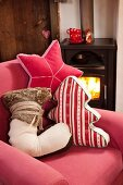 Winterliche DIY-Dekokissen in Baumform, Sternenform und Stiefelform auf rotem Sofa