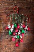 DIY-Adventskalender mit nummerierten Säckchen an rotem Kleiderbügel aufgehängt