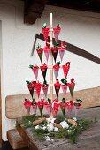 DIY-Adventskalender mit Holzständer und nummertierten Spitztüten auf rustikalem Holztisch
