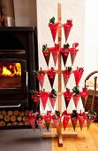 Hand-made Advent calendar with numbered cones in wooden stand next to cosy fire