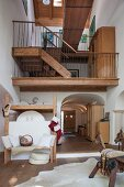 Hallway with landings and bed above masonry stove in renovated farmhouse