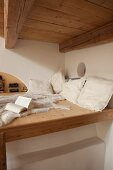 Crocheted cushions and animal-skin rug on wooden loft bed above masonry stove