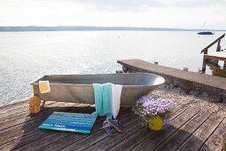 Zinkbadewanne mit DIY-Badematte aus lackierten Holzleisten auf Holzterrasse am See