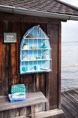Maritime accessories on hand-made wall-mounted shelves hung on outside wall of boat house