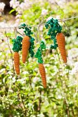 Hand-made crocheted carrots hung from washing line in garden