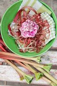 Rhubarb stalks next to carnation and rhubarb peel in green bowl