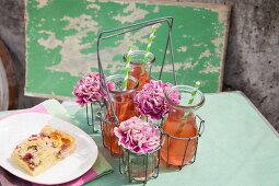Carafes of rhubarb juice and carnations in drinking glasses in bottle carrier