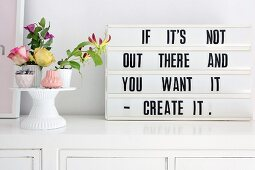 Retro-style motto in frame next to flower arrangement