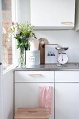 Kitchen scales, glass vase of flowers and bread bin on white kitchen cabinets