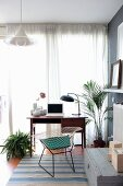 Retro desk, classic chair and houseplants in front of window