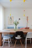 Various chairs around solid wooden dining table, flowers in large glass jar, eye chair on wall and crocheted garland