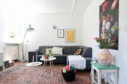 White crocheted blanket and scatter cushions on grey couch in retro living room