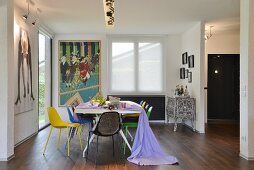 Colourful chairs, length of lilac fabric, artistic ethnic cabinet and modern artwork in dining area