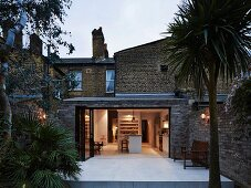 View past large yucca palm to extension of traditional brick house with illuminated interior at twilight