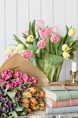 Bouquets of tulips wrapped in paper and in glass vase next to stack of books