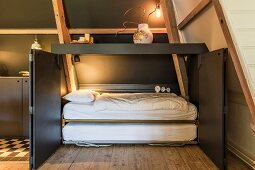 Fold-away bed in dark grey cupboard with open doors