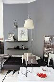 Candlesticks and strawberries on table in modern living room in shades of grey