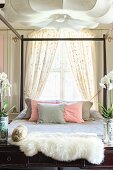 Sheepskin and orchids on console table and wood-framed bed in front of window