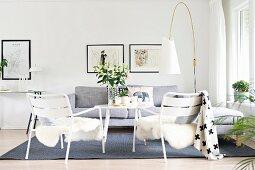 Weisse Gartenstühle mit Tierfell, hellgraue Polstercouch und Designer-Stehleuchte im Loungebereich
