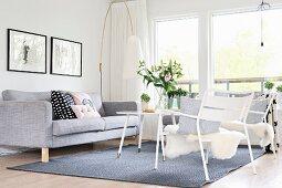 Hellgraue Polstercouch, Designer-Stehleuchte und weisse Gartenstühle mit Tierfell vor dem Fenster im Loungebereich