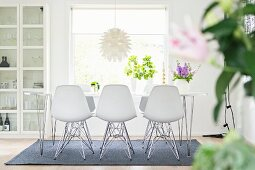 White shell chairs around dining table in front of window
