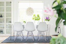Weisse Schalenstühle um Esstisch vor dem Fenster