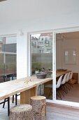 Langer Holztisch mit Baumstamm-Hockern auf der Terrasse