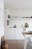 Blick auf weisse Einbauküche mit offenem Regal