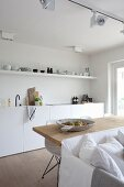 Weisse Einbauküche mit offenem Regal und langem Esstisch aus Holz