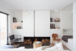 Offener, weisser Wohnraum mit Kamin und Schlafbereich in kleinem Apartment