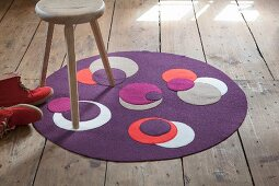 Round, purple, boiled-wool rug with contrasting appliqué circles