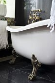 Free-standing, vintage bathtub with brass claw feet on black tiled floor