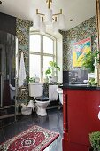 Toilet below window and Oriental rug on black tiled floorr in vintage bathroom