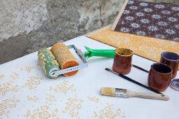 Strukturwalze, Pinsel, Keramikbecher und verschiedene Musterplatten