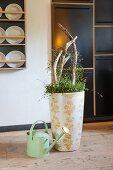 Mit Blumenmuster dekorierte Bodenvase neben Giesskanne