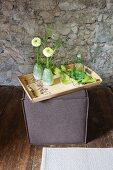 Holztablett mit DIY-Blumenmuster verziert auf Sitzwürfel vor Natursteinwand