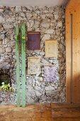 Nostalgische Blumenmotive auf Sperrholzplatten gewalzt an Natursteinwand aufgehängt