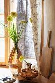 Arrangement mit Glasvasen und Blumendekoration vor bedrucktem Vorhang