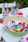 Various sewing utensils (yarn, ties, pins, scissors) in a bowl and boxes on a table outdoors