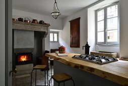 Gas hob on kitchen counter in front of fireplace in kitchen of 19th-century Italian villa