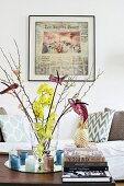 Flowers in glass vase, candles and stacked books in front of framed newspaper pages and couch