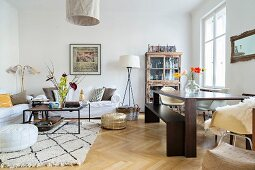 Woollen rug and oak parquet flooring in open-plan living area of period apartment