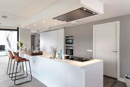 A modern white kitchen with an island with an illuminated, suspended ceiling panel and a extractor hood