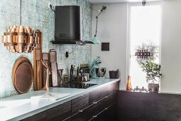 Various wooden trays on kitchen counter below blue patterned wall tiles