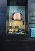 Pendant lamp against patterned wall tiles in niche in black fitted kitchen cupboards