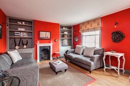 Elegant living room with red walls, fitted shelving and open fireplace