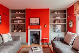 Red walls, grey fitted shelving and vintage fireplace in living room