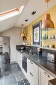 Kitchen counter with granite worksurface below shelves mounted on yellow wall